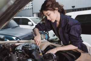 A lady mechanic repairing the car engine